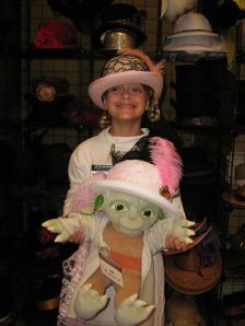 girl and toy yoda wearing Victorian hats