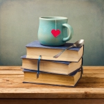 Old vintage books and cup with heart shape on wooden table
